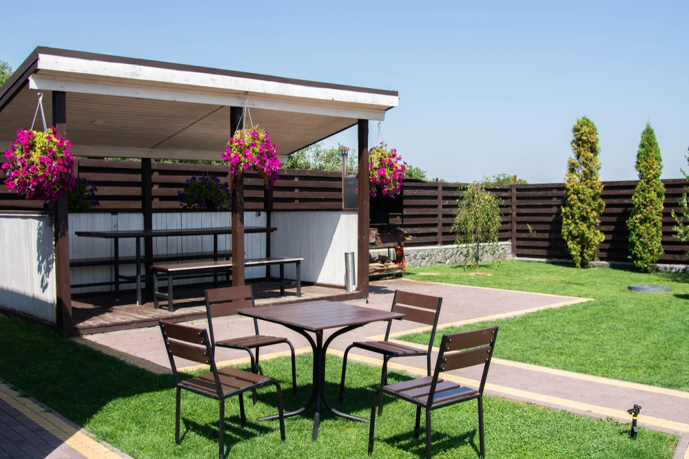 Outdoor wooden retractable pergola over seating.