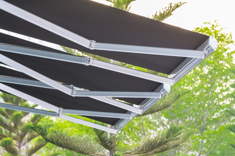 Black outdoor awning with a silver frame and tree background.